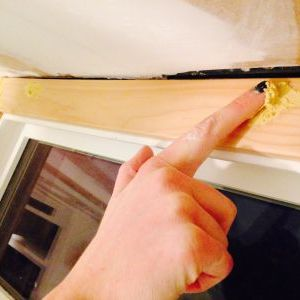 Applying wood putty to ceiling window trim