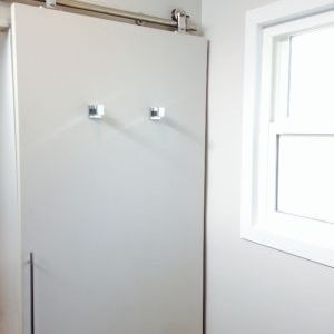 Sliding Barn Door With Towel Hooks In Bathroom
