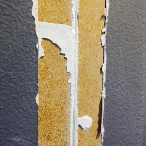 Removing drywall tape after cracks appeared because tape didn't stick to hardboard panels