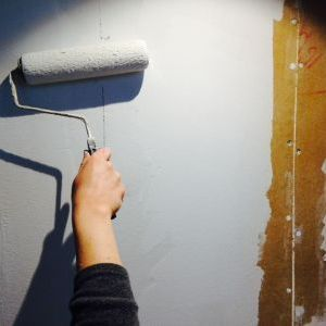 Priming remodeled living room wall panels after removing paint and drywall tape