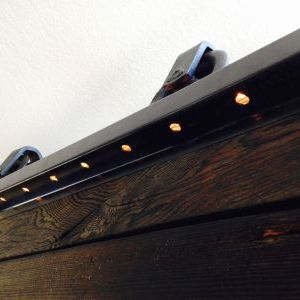 Bottom view of rope lights shining through drilled out spot welds on barn door